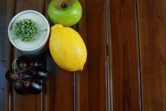 Φρέσκα υγρά φρούτα: λεμόνι, πράσινα μήλο και σταφύλια με τη διακόσμηση στο μαύρο υπόβαθρο Στοκ Εικόνες
