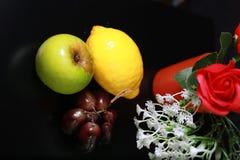 Φρέσκα υγρά φρούτα: λεμόνι, πράσινα μήλο και σταφύλια με τη διακόσμηση στο μαύρο υπόβαθρο Στοκ Φωτογραφίες