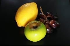 Φρέσκα υγρά φρούτα: λεμόνι, πράσινα μήλο και σταφύλια με τη διακόσμηση που απομονώνεται στο μαύρο υπόβαθρο Στοκ Εικόνες