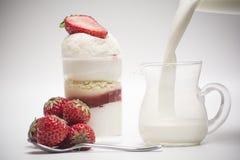 Φρέσκα φράουλα και επιδόρπιο Χύστε το γάλα μέσα στο ποτήρι Στοκ φωτογραφία με δικαίωμα ελεύθερης χρήσης