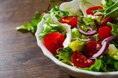 Φρέσκα φύλλα σαλάτας μιγμάτων με την ντομάτα στο κύπελλο στο ξύλινο υπόβαθρο Στοκ Εικόνες
