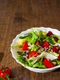 Φρέσκα φύλλα σαλάτας μιγμάτων με την ντομάτα στο κύπελλο στο ξύλινο υπόβαθρο Στοκ Φωτογραφία