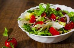 Φρέσκα φύλλα σαλάτας μιγμάτων με την ντομάτα στο κύπελλο στο ξύλινο υπόβαθρο Στοκ φωτογραφίες με δικαίωμα ελεύθερης χρήσης