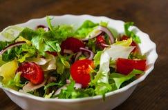 Φρέσκα φύλλα σαλάτας μιγμάτων με την ντομάτα στο κύπελλο στο ξύλινο υπόβαθρο Στοκ Φωτογραφίες