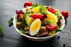 Φρέσκα φύλλα σαλάτας μιγμάτων με την ντομάτα, τα αυγά και την ελιά στο κύπελλο στο σκοτεινό ξύλινο υπόβαθρο Στοκ εικόνα με δικαίωμα ελεύθερης χρήσης