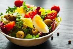 Φρέσκα φύλλα σαλάτας μιγμάτων με την ντομάτα, τα αυγά και την ελιά στο κύπελλο στο σκοτεινό ξύλινο υπόβαθρο Στοκ Εικόνες