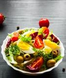 Φρέσκα φύλλα σαλάτας μιγμάτων με την ντομάτα, τα αυγά και την ελιά στο κύπελλο στο σκοτεινό ξύλινο υπόβαθρο Στοκ Εικόνα