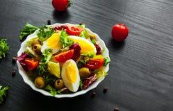 Φρέσκα φύλλα σαλάτας μιγμάτων με την ντομάτα, τα αυγά και την ελιά στο κύπελλο στο σκοτεινό ξύλινο υπόβαθρο Στοκ φωτογραφίες με δικαίωμα ελεύθερης χρήσης