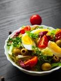 Φρέσκα φύλλα σαλάτας μιγμάτων με την ντομάτα, τα αυγά και την ελιά στο κύπελλο στο σκοτεινό ξύλινο υπόβαθρο Στοκ φωτογραφία με δικαίωμα ελεύθερης χρήσης