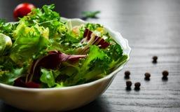 Φρέσκα φύλλα σαλάτας μιγμάτων με το μαρούλι, το radicchio, και τον πύραυλο στο κύπελλο στο σκοτεινό ξύλινο υπόβαθρο Στοκ Εικόνα