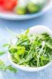 Φρέσκα φύλλα arugula στο κύπελλο στον πίνακα Ελαφριά ανασκόπηση Στοκ Φωτογραφίες