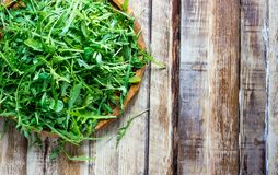 Φρέσκα φύλλα arugula στο ξύλινο κύπελλο Στοκ Εικόνες