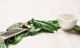 Φρέσκα φύλλα σπανακιού με τη σχάρα, το μοσχοκάρυδο και το κύπελλο του πετρελαίου άσπρο σε ξύλινο Στοκ Εικόνα