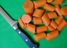 Φρέσκα χοντρά κομμάτια καρότων που κόβονται στο πράσινο υπόβαθρο με το μαχαίρι Στοκ φωτογραφία με δικαίωμα ελεύθερης χρήσης