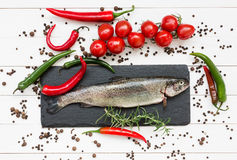 Φρέσκα ψάρια πεστροφών στον τέμνοντα πίνακα με τις ντομάτες κερασιών Στοκ Εικόνες