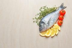 Φρέσκα ψάρια dorado με το θυμάρι, τις φέτες λεμονιών και τις ντομάτες Στοκ Φωτογραφίες