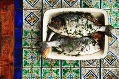 Φρέσκα bream ψάρια στον πίνακα χρωματισμένων των χέρι κεραμιδιών Στοκ Εικόνες