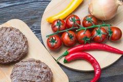 Φρέσκα burgers beaf στον τέμνοντα πίνακα με την ντομάτα, το πιπέρι και το onio Στοκ Φωτογραφία