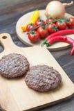 Φρέσκα burgers beaf στον τέμνοντα πίνακα με την ντομάτα, το πιπέρι και το onio Στοκ Εικόνα