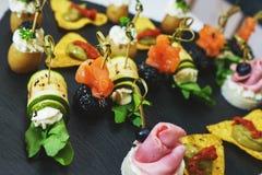 Φρέσκα canaps και πρόχειρα φαγητά στον πίνακα στρέψτε μαλακό Στοκ Εικόνες