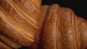 Φρέσκα croissants στο μαύρο υπόβαθρο Επίδραση θαμπάδων Κλείστε επάνω την όψη φιλμ μικρού μήκους
