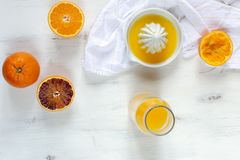 Φρέσκα juicy πορτοκάλια, φρέσκος συμπιεσμένος χυμός από πορτοκάλι, αναζωογονώντας θερινό ποτό, άσπρο ξύλινο υπόβαθρο στοκ φωτογραφία