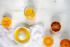 Φρέσκα juicy πορτοκάλια, φρέσκος συμπιεσμένος χυμός από πορτοκάλι, αναζωογονώντας θερινό ποτό, άσπρο ξύλινο υπόβαθρο στοκ εικόνα