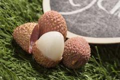 Φρέσκα lychees στο υπόβαθρο χλόης Στοκ Εικόνες