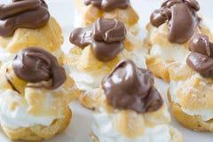 Φρέσκα profiteroles με την κρέμα και τη σοκολάτα Στοκ Εικόνες