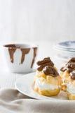 Φρέσκα profiteroles με την κρέμα και τη σοκολάτα Στοκ Εικόνα