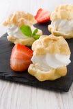 Φρέσκα profiteroles με την κρέμα και τη φράουλα στο ξύλο Στοκ Εικόνες