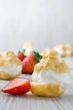 Φρέσκα profiteroles με την κρέμα και τη φράουλα στο ξύλο Στοκ Εικόνα