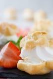Φρέσκα profiteroles με την κρέμα και τη φράουλα στο ξύλο Στοκ εικόνα με δικαίωμα ελεύθερης χρήσης