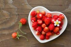 Φρέσκες άγριες φράουλες σε ένα φλυτζάνι με μορφή μιας καρδιάς, σύμβολο της αγάπης Ξύλινη ανασκόπηση κορυφαία όψη Στοκ φωτογραφίες με δικαίωμα ελεύθερης χρήσης