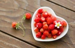 Φρέσκες άγριες φράουλες σε ένα φλυτζάνι με μορφή μιας καρδιάς, σύμβολο της αγάπης Ξύλινη ανασκόπηση κορυφαία όψη Στοκ Εικόνα