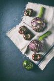 Φρέσκες αγκινάρες, πράσινες και μαύρες ντομάτες στο κλωστοϋφαντουργικό προϊόν λινού r στοκ φωτογραφίες με δικαίωμα ελεύθερης χρήσης