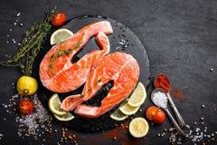 Φρέσκες ακατέργαστες μπριζόλες ψαριών σολομών κόκκινες στο μαύρο υπόβαθρο Στοκ Φωτογραφίες