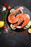 Φρέσκες ακατέργαστες μπριζόλες ψαριών σολομών κόκκινες στο μαύρο υπόβαθρο Στοκ φωτογραφίες με δικαίωμα ελεύθερης χρήσης
