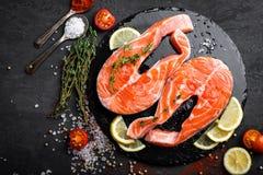 Φρέσκες ακατέργαστες μπριζόλες ψαριών σολομών κόκκινες στο μαύρο υπόβαθρο Στοκ εικόνες με δικαίωμα ελεύθερης χρήσης