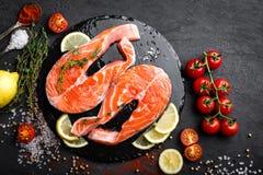 Φρέσκες ακατέργαστες μπριζόλες ψαριών σολομών κόκκινες στο μαύρο υπόβαθρο Στοκ φωτογραφία με δικαίωμα ελεύθερης χρήσης