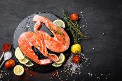 Φρέσκες ακατέργαστες μπριζόλες ψαριών σολομών κόκκινες στο μαύρο υπόβαθρο Στοκ Εικόνες