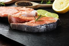 Φρέσκες ακατέργαστες μπριζόλες ψαριών σολομών με τα φρέσκα χορτάρια στην πέτρα backgroun Στοκ Φωτογραφία