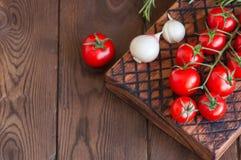 Φρέσκες ακατέργαστες ντομάτες κερασιών σε έναν ξύλινο πίνακα με το σκόρδο πιπεριών Στοκ φωτογραφία με δικαίωμα ελεύθερης χρήσης