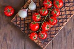 Φρέσκες ακατέργαστες ντομάτες κερασιών σε έναν ξύλινο πίνακα με το σκόρδο πιπεριών Στοκ εικόνα με δικαίωμα ελεύθερης χρήσης