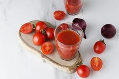 Φρέσκες ακατέργαστες ντομάτες, κρεμμύδι και ποτήρι κερασιών του νόστιμου χυμού ντοματών στο μαρμάρινο πίνακα στην κουζίνα στοκ φωτογραφία με δικαίωμα ελεύθερης χρήσης