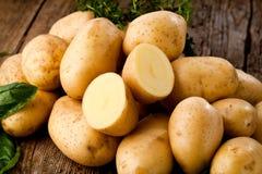 Φρέσκες ακατέργαστες οργανικές πατάτες στο παλαιό εκλεκτής ποιότητας υπόβαθρο στοκ εικόνες
