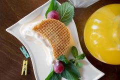 Φρέσκες βάφλες με το παγωτό σε ένα άσπρο πιάτο στο ξύλινο υπόβαθρο Στοκ εικόνα με δικαίωμα ελεύθερης χρήσης