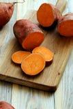 Φρέσκες γλυκές πατάτες στο επιτραπέζιο υπόβαθρο κουζινών Στοκ Φωτογραφίες