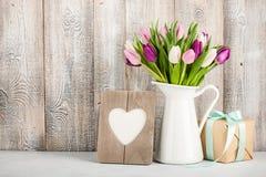 Φρέσκες ζωηρόχρωμες τουλίπες σε μια κανάτα, ένα κιβώτιο δώρων και διαμορφωμένο ένα καρδιά πλαίσιο στοκ εικόνα