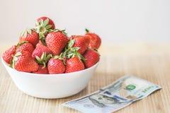 Φρέσκες θερινές φράουλες σε ένα άσπρο πιάτο στον πίνακα με το τραπεζογραμμάτιο monye εκατό δολάρια Η έννοια των υγιών τροφίμων κα Στοκ εικόνες με δικαίωμα ελεύθερης χρήσης